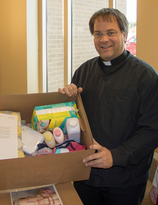 Fr. Kayser with the boxes for babies